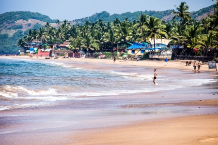 exiting: Exiting Anjuna beach panorama on low tide with white wet sand and green coconut palms, Goa, India