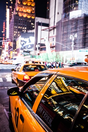 time of the year: Yellow cab speeds through Times Square in New York, NY, USA.  Stock Photo