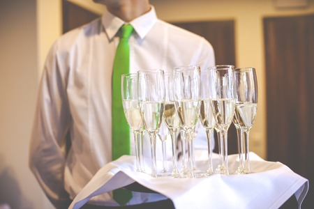 professional waiter in uniform is serving wine photo