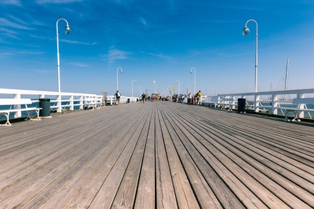baltic people: SOPOT, POLAND - 9 AUGUST: People on Sopot molo at Baltic Sea, 9 august 2014. Sopot is major health and tourist resort destination and this pier with 511.5 meters long is the longest wooden pier in Europe.  Editorial