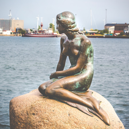 The Little Mermaid is a bronze statue by Edvard Eriksen, depicting a mermaid. The sculpture is displayed on a rock by the waterside at the Langelinie promenade in Copenhagen, Denmark  photo