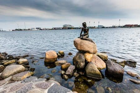 The Little Mermaid is a bronze statue by Edvard Eriksen, depicting a mermaid. The sculpture is displayed on a rock by the waterside at the Langelinie promenade in Copenhagen, Denmark