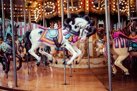 古フランス語のカルーセル ・ ホリデー ・ パークで。3 つの馬と伝統的な見本市会場ビンテージ カルーセル上の航空機。馬とメリーゴーランド。