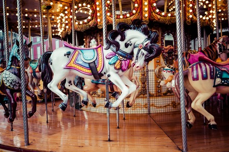Old French carousel in a holiday park. Three horses and airplane on a traditional fairground vintage carousel. Merry-go-round with horses. photo