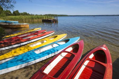 lakeshore: Colorful kayaks moored on lakeshore, Goldopiwo Lake, Mazury, Poland.