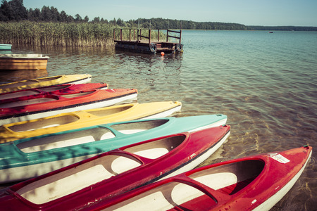 moored: Colorful kayaks moored on lakeshore, Goldopiwo Lake, Mazury, Poland.