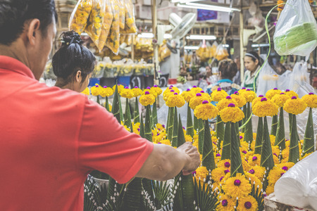 silom: BANGKOK, THAILAND - NOVEMBER 07, 2015: Local woman sells Thai style garland (Phuang Malai) at a market near Silom road, Bangkok, Thailand