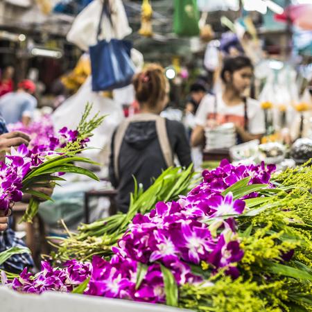 identidad cultural: Ramos de flores de orqu�deas p�rpuras y blancas apiladas en exhibici�n en el mercado de flores en Bangkok, Tailandia