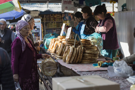 pastil: BISHKEK, KYRGYZSTAN - SEPTEMBER 27, 2015 : Woman selling Asian style bread in local market. Editorial