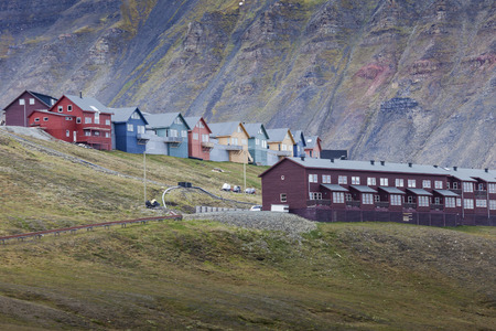 case colorate: Idyllic scenic view, colorful houses and green field with arctic flowers against the background of dramatic sky and barren mountain in Longyearbyen, Spitsbergen archipelago (Svalbard), Norway, Europe