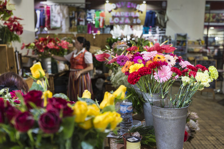 june 25: Funchal, Portugal - June 25: The florist dressed in traditional outfit at Farmers Market on June 25, 2015 in Funchal, Portugal. Editorial