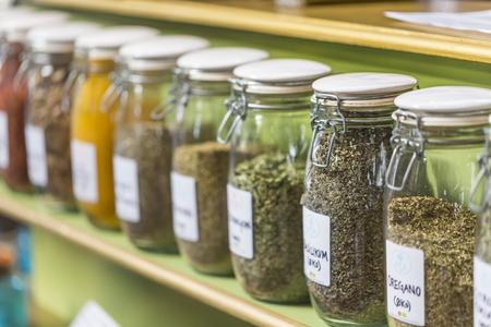 herbolaria: surtido de frascos de vidrio en los estantes de tienda de herbolario en Marrakech, Marruecos, que contienen hierbas y especias con fines medicinales y culinarias