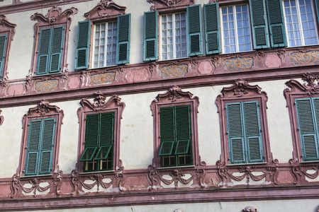 flower boxes: Old italian windows, open, in a faded painted wall with shutters, flower boxes and geraniums