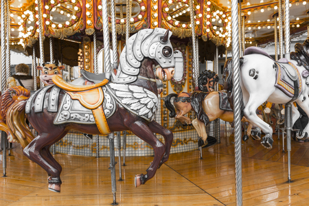 fairground: Old French carousel in a holiday park. Three horses and airplane on a traditional fairground vintage carousel. Merry-go-round with horses.