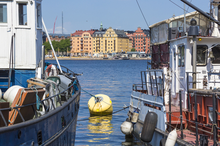 water s edge: Old city buildings and old boats on water under blue sky in Stockholm, Sweden.