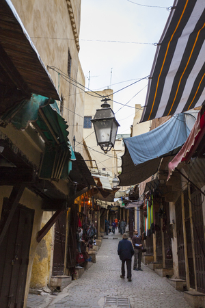 souk: Picturesque small street in souk of Fez medina (old town) with muslim and tourists