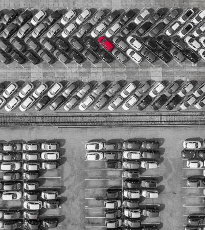white colour: Aerial view lot of vehicles on parking for new car. Black and White selective red colour.