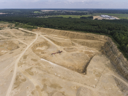 extracted: Aerial view of excavator and truck working on the field of sand mine in Poland.