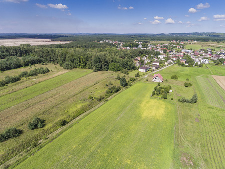 Rural landscape with green hill and blue sky in Poland. View from above.