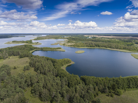 masuria: View of small islands on the lake in Masuria and Podlasie district, Poland. Blue water and whites clouds. Summer time. View from above.