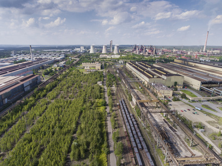 steelworks: Steel factory with smokestacks at sunny day.Metallurgical plant. steelworks, iron works. Heavy industry in Europe.Air pollution from smokestacks, ecology problems. Industrial landscape.View from above. Stock Photo