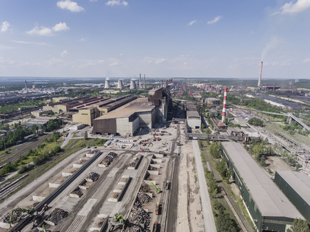 Steel factory with smokestacks at sunny day.Metallurgical plant. steelworks, iron works. Heavy industry in Europe.Air pollution from smokestacks, ecology problems. Industrial landscape.View from above. Stock Photo