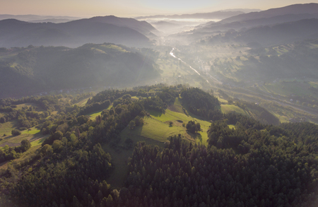 valley below: Landscape misty panorama. Fantastic dreamy sunrise on rocky mountains with view into misty valley below. Foggy forest hills. View from above. Ochotnica Dolna village, Poland.