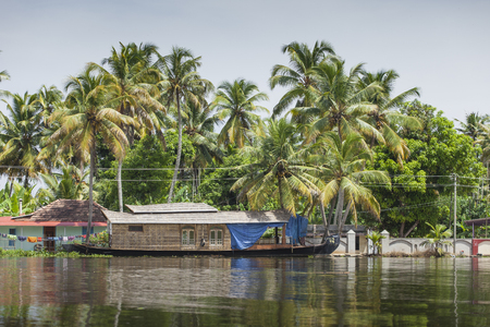 alleppey: ALLEPPEY, KERALA, INDIA - AUGUST 16, 2016: Unidentified indian people in small boat in backwaters. Kerala backwaters are both major tourist attraction and integral part of local people life in Kerala
