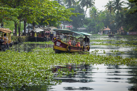 ALLEPPEY, KERALA, INDIA - AUGUST 16, 2016: Unidentified indian people in small boat in backwaters. Kerala backwaters are both major tourist attraction and integral part of local people life in Kerala