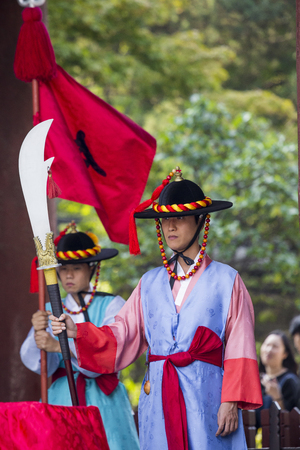 impassive: SEOUL, SOUTH KOREA - OCTOBER 20, 2016: Palace guards in traditional costumes solemnly guard the imposing main gate of Deoksugung Palace in downtown Seoul, South Korea. Editorial