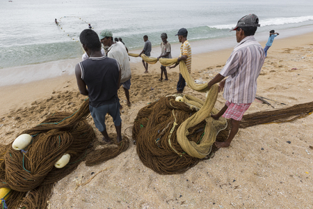 water s edge: GALLE, SRI LANKA - DECEMBER 09, 2016 : Fishermen stood and work in the a boat on the beach at Galle city on December 12, 2016, Fishermen on beach in the morning for sald many fish at Galle, Sri lanka.