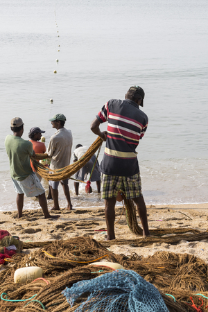 GALLE, SRI LANKA - DECEMBER 09, 2016 : Fishermen stood and work in the a boat on the beach at Galle city on December 12, 2016, Fishermen on beach in the morning for sald many fish at Galle, Sri lanka.