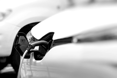 Cable hanging down from gas tank location on electrical vehicle. Outdoors   Stock Photo