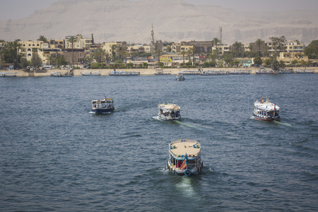 Wooden boats carrying passengers docked along the Nile River in Aswan, Egypt, North Africa