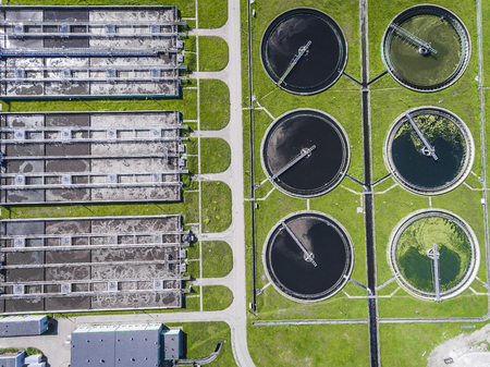 clarifying: Sewage farm. Static aerial photo looking down onto the clarifying tanks and green grass. Geometric background texture.