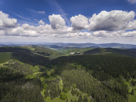 sudetes: Aerial view of the summer time in mountains near Czarna Gora mountain in Poland. Pine tree forest and clouds over blue sky. View from above.
