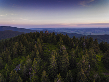 Sunset. Aerial view of the summer time in mountains near Czarna Gora mountain in Poland. Pine tree forest and clouds over blue sky. View from above.