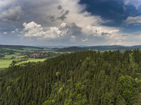 sudetes: Aerial view of the summer time in mountains near Stronie Slaskie town in Poland. Pine tree forest and clouds over blue sky. View from above.