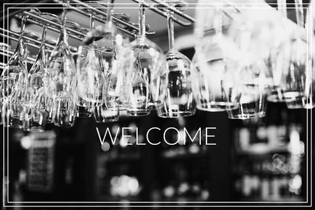 Welcome. Empty glasses for wine above a bar rack
