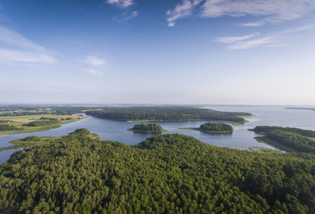masuria: Aerial view of green islands and clouds at summer sunny morning. Masurian Lake District  in Poland. Stock Photo