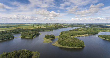 Aerial view of green islands and clouds at summer sunny day.Wydminy lake on Masuria in Poland. Stock Photo