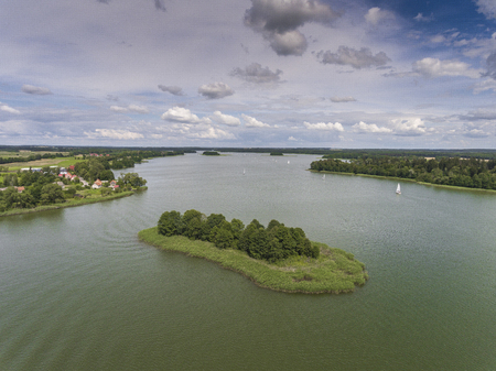 Aerial view of green islands and clouds at summer sunny morning. Masurian Lake District  in Poland. Wonders of the world from above. Yachts sailing in the lake.