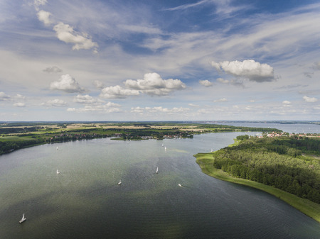 lake district: Aerial view of green islands and clouds at summer sunny morning. Masurian Lake District  in Poland. Wonders of the world from above. Yachts sailing in the lake.