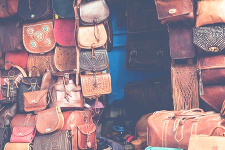 Marokkaanse lederen goederenzakken en pantoffels bij openluchtmarkt in Marrakech, Marokko. Stockfoto