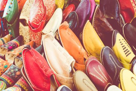 Alineación colorida de los zapatos marroquíes en una tienda. Zapatos orientales en un bazar. Zapatillas marroquíes multicolores. Zapatillas de cuero coloridas en venta en el zoco de Marrakech. Foto de archivo - 92531013