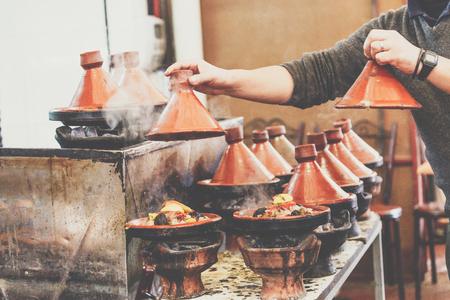 Cooking of meat in traditional Moroccan ceramic tajine dish, Marrakesh, Morocco