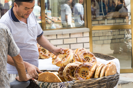 MARGILAN, UZBEKISTAN - AUGUST 24, 2018: National plain uzbek bread sold in the market - Margilan near Fergana, Uzbekistan.