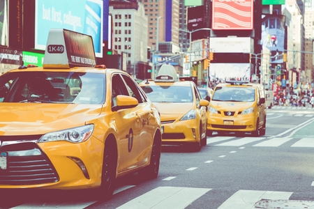 NEW YORK - SEPTEMBER 2, 2018: Yellow cab speeds through Times Square the busy tourist intersection of neon art and commerce and is an iconic street of New York City, USA. Editorial