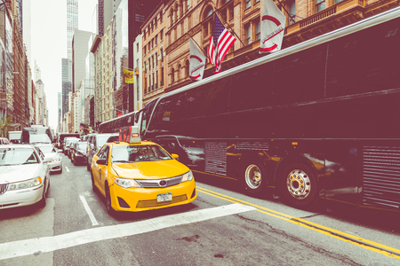 NEW YORK - SEPTEMBER 2, 2018: Yellow cab speeds through Times Square the busy tourist intersection of neon art and commerce and is an iconic street of New York City, USA 에디토리얼