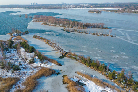 Aerial view of frozen lake. Winter scenery. Landscape photo captured with drone above winter wonderland.